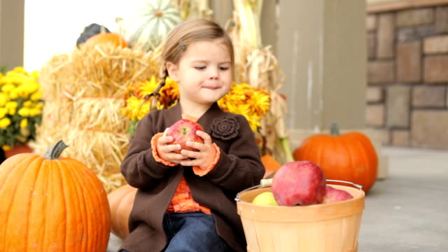 Young girl in Autumn sitting on porch with apple HD 1080p: Young girl in Autumn sitting on porch with apple porch stock videos & royalty-free footage