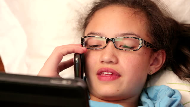 Young girl in bed using smart phone and tablet video