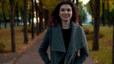 giovane ragazza in camice a piedi nel parco autunnale e sorridente al rallentatore - capelli castani video stock e b–roll