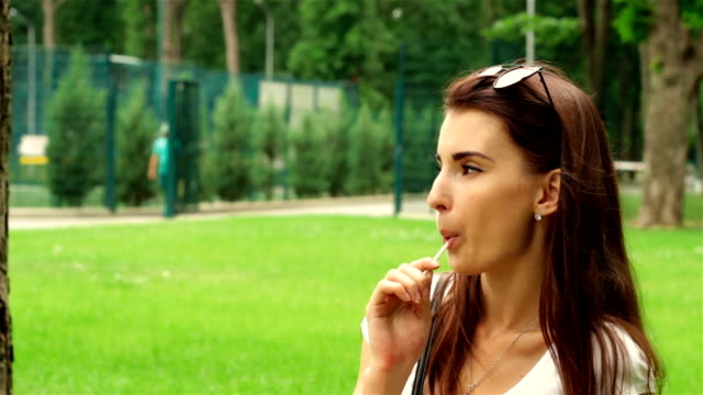 young girl in glasses on her head sits in the Park and sucks lollipop video