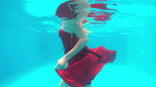 Young girl in long red dress walking along bottom of the pool under water video