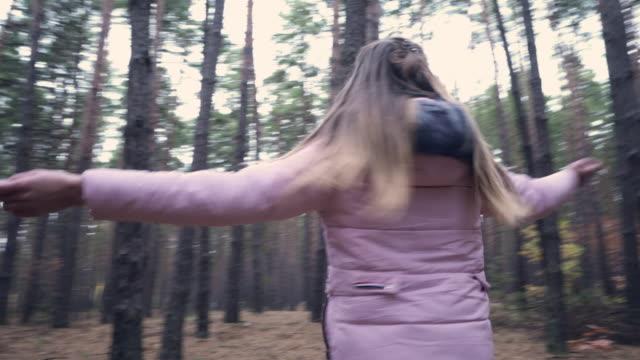 ung flicka i rosa kappa som snurrar runt i höstens skog - endast en tonårsflicka bildbanksvideor och videomaterial från bakom kulisserna
