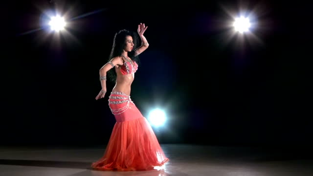 Young girl in pink oriental costume dancing belly dance, on black, back light, slow motion video