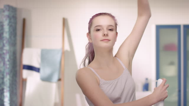Young girl in puberty using antiperspirant in a modern bathroom video