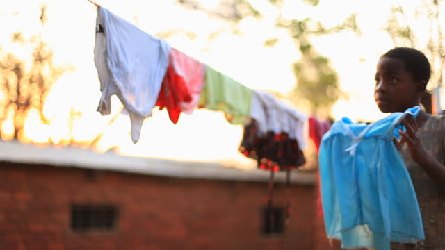 Young girl in rural African village hanging up laundry video