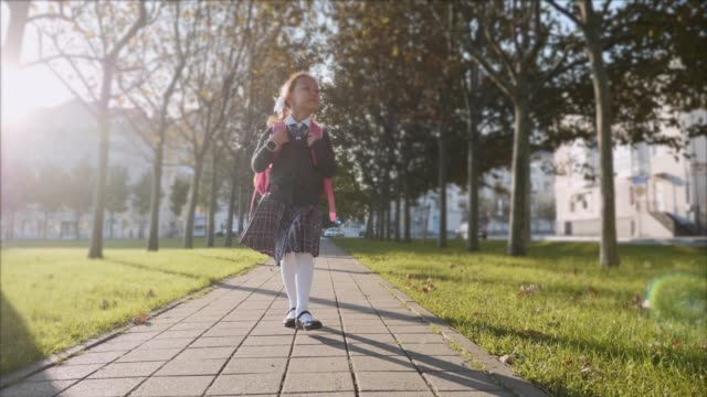 Young girl in school uniform is walking in the park at sunny weather, steadicam. Young blonde girl with a pink backpack in school uniform is walking quickly in the park on path at sunny autumn weather, looking around and smiling. Trees along the way, front view, steadicam shot. wisdom stock videos & royalty-free footage