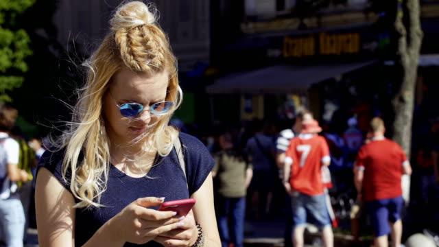 vídeos de stock e filmes b-roll de young girl in sunglasses using phone - soccer supporter portrait