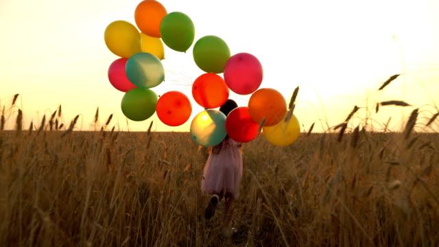 カラフルな風船とドレスの若い女の子は、フィールドを横切って実行されています。 ビデオ