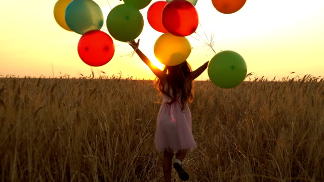 vídeos de stock e filmes b-roll de young girl in the dress with colorful ballons is running across the field. - mulher balões