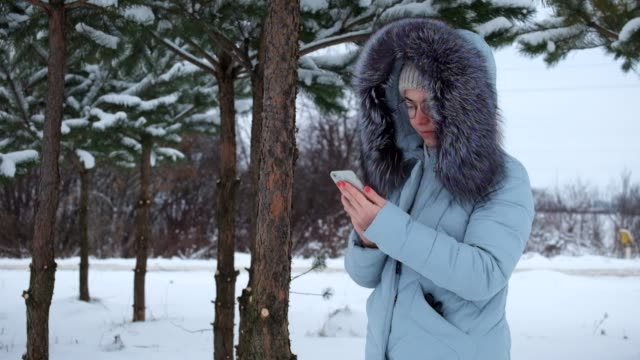Young girl in the hood is standing in a winter pine grove and is looking for something in the phone video