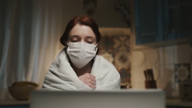 vídeos de stock e filmes b-roll de young girl in the kitchen with laptop. young woman working remotely at home because of pandemic. woman in medical mask. - covid hair