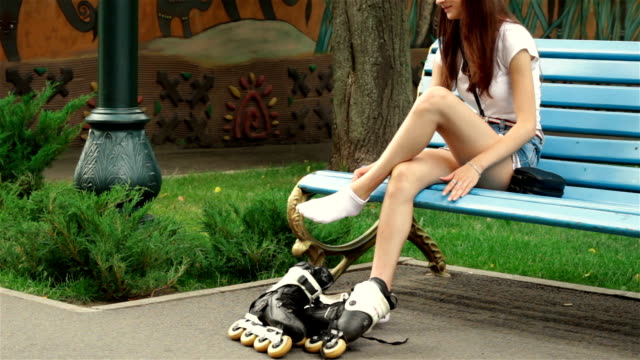 young girl in the Park on a bench is shooting rollers Slim young girl in the Park on a bench is shooting rollers charming stock videos & royalty-free footage