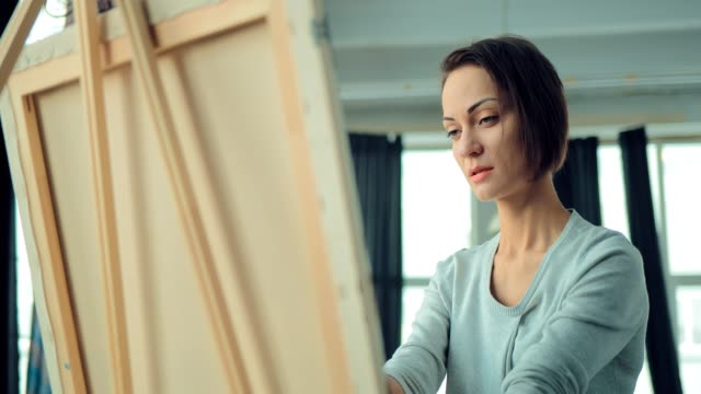 young girl inspired paints a picture on the easel. woman draws in the bright workshop. portrait view. - cavalletto attrezzatura per arti e mestieri video stock e b–roll