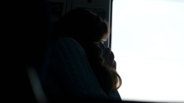 Young girl is calling on the phone during riding in train. Woman travelling on railway and talking on smartphone. Female looking to window and speaking on cellphone video