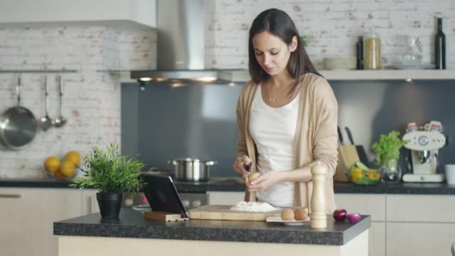 vídeos y material grabado en eventos de stock de chica joven es cocinar en la cocina. ella para la referencia de la receta en su tablet pc y se rompe un huevo en un montón de harina medido. - woman cooking