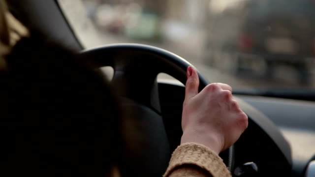 Young girl is driving a car in winter in the city.