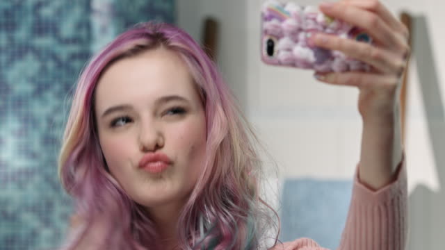 Young girl is having fun in the bathroom while taking photos with grimaces video