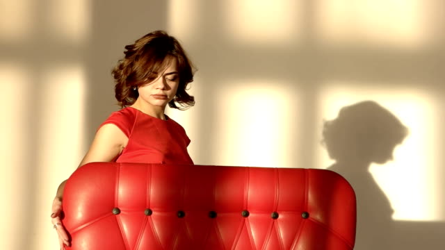 A young girl is sad and depressing. The woman touches the red armchair. video