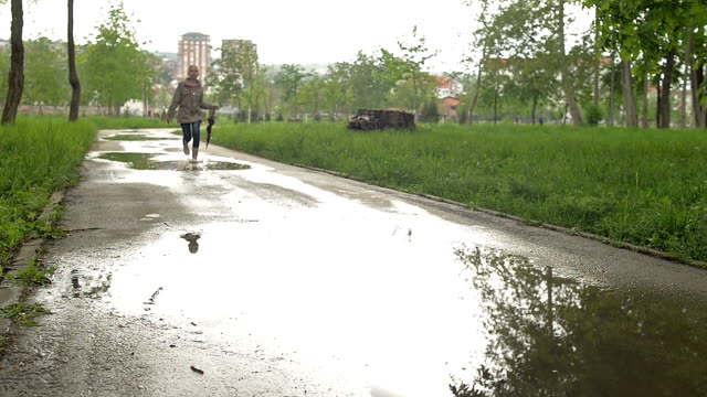 Young girl jumping in puddles with umbrella video