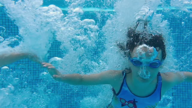828b6aa19a7 Young girl jumping into swimming pool in amazing slow motion video