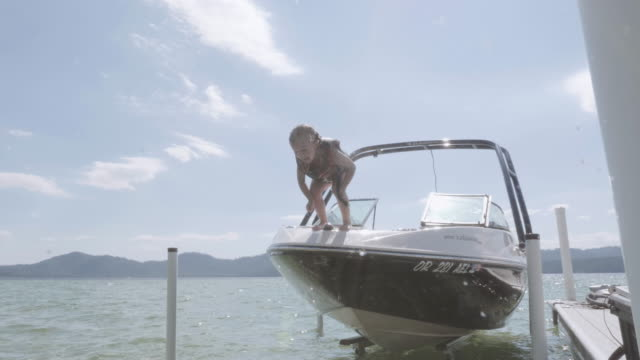 4K SLO MO: Young girl jumping off a ski boat into the water - video