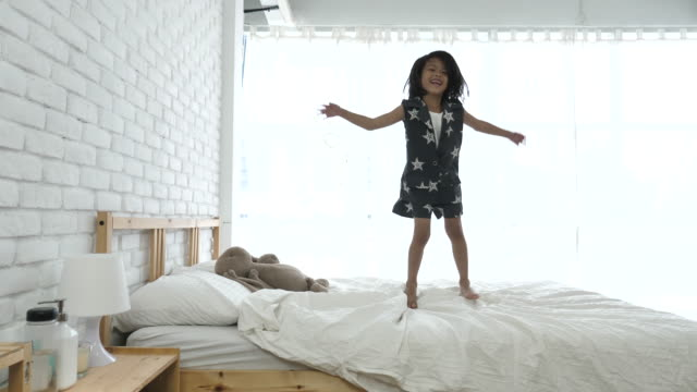 Young Girl Jumping On Bed, Slow motion video