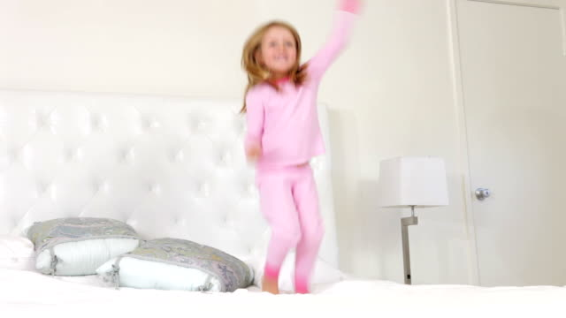young girl jumping on bed - pajamas stock videos & royalty-free footage