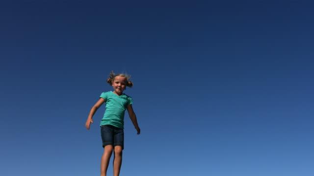 giovane ragazza saltando sul trampolino, rallentatore - saltare video stock e b–roll