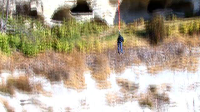 молодая девушка прыжки со скалы - банджи джампинг стоковые видео и кадры b-roll