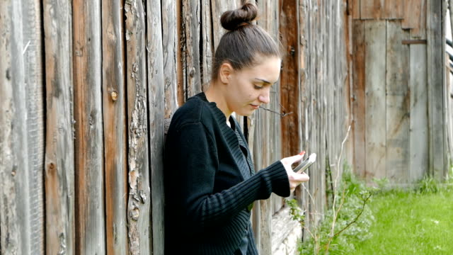 Young girl leaning on an old barn and using her smart phone video
