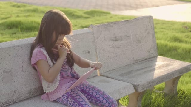 Young Girl Learning on Tablet at Park