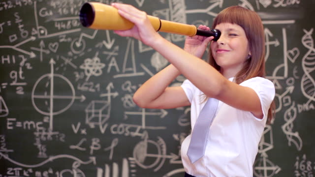 Young girl learning playfully in frot of a big blackboard with telescope video