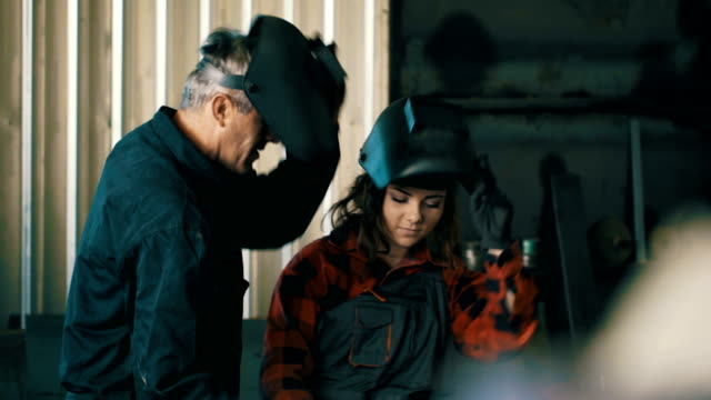 Young girl learns to using a welding machine Young girl learns to using a welding machine metal worker stock videos & royalty-free footage