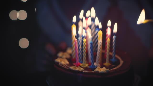 Young girl lighting 16 candles on birthday cake