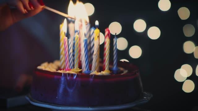어린 소녀 조명 16 생일 케이크에 촛불 - 촛불 조명 장비 스톡 비디오 및 b-롤 화면