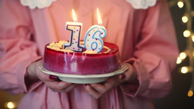 Young girl lighting 16 candles on birthday cake