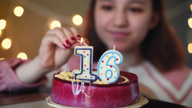 Young girl lighting candles on birthday cake