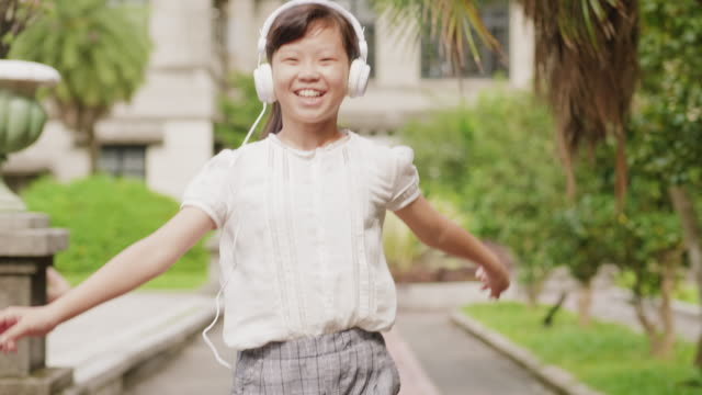 a young girl listening to music in a public park in taiwan - capelli neri video stock e b–roll