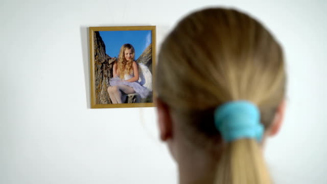 Young girl looking at photograph of a little girl in photo frame on the wall video