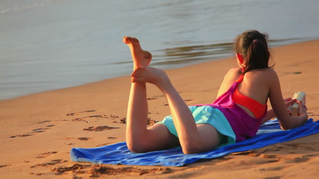 Young girl lying on tropical beach reading book video