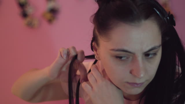 Young girl making braids in her bedroom