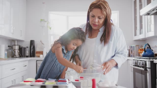 Young girl making cakes with her grandmother, filling cake forms with cake mis using spoon, close up Young girl making cakes with her grandmother, filling cake forms with cake mis using spoon, close up granddaughter stock videos & royalty-free footage