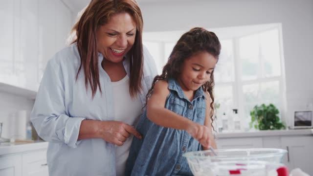 young girl making cakes with her mum and grandmother filling cake forms with mix, close up, handheld - piec przygotowywać jedzenie filmów i materiałów b-roll