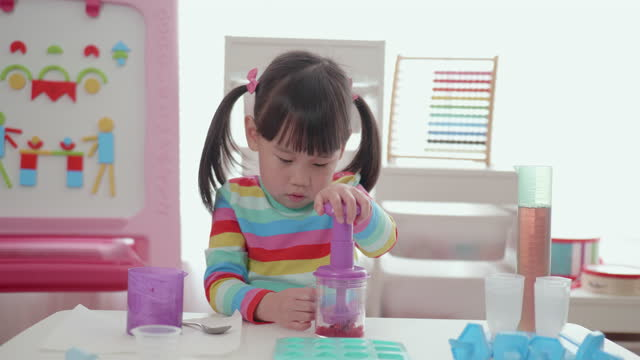 young girl making frozen yogurt raspberry gems for home schooling