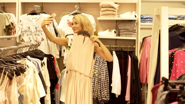 a young girl making selfie on the phone trying on clothes in the clothing store. - modella negozio video stock e b–roll