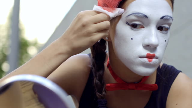 young girl mime correct white mask on her face with wet napkin - гримировальные краски стоковые видео и кадры b-roll