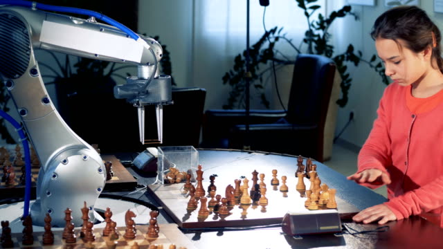 vídeos de stock e filmes b-roll de young girl moves chess figure playing with a modern automated chess robot. 4k. - xadrez