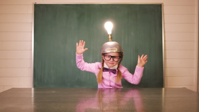 young girl nerd uses thinking cap for big idea - solo una bambina femmina video stock e b–roll