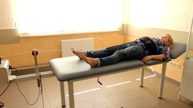 vídeos y material grabado en eventos de stock de chica joven en un procedimiento para la tracción de la columna vertebral. - columna vertebral humana