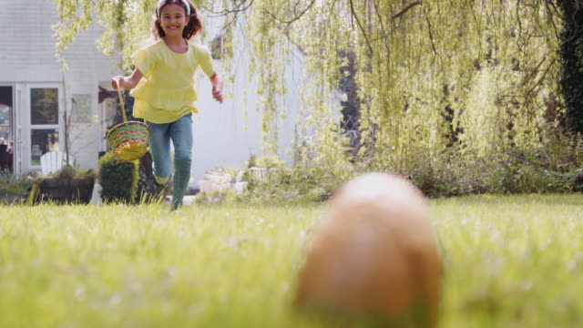 Young girl on Easter egg hunt running across garden and picking up chocolate egg to put into basket - shot in slow motion